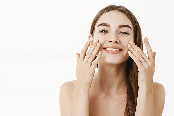 charming-relaxed-gentle-young-woman-making-cosmetological-procedure-applying-facial-cream-face-with-fingers-smiling-broadly-feeling-perfect-taking-care-skin.jpg